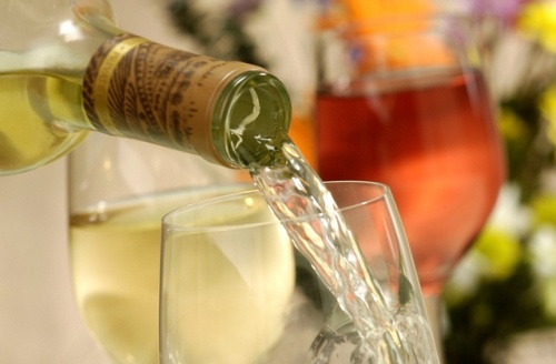 Close up shot, pouring chardonnay wine into a glass, two other glasses and flowers in background